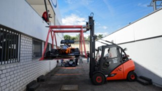 Linde Mietstapler befördert vorsichtig eine Rennwagen